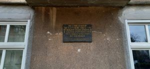 Tablica pamiątkowa na frontowej ścianie dawnej szkoły.